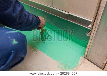 Worker Is Painting By Brush With Green Colored  Waterproof Finish Material The Bathroom Floor In Apa