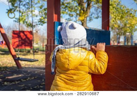Adorable infant boy at playhouses in public playground, Zagreb, Croatia. poster