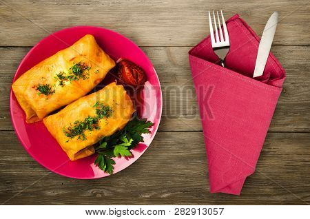 Cabbage Rolls In A Plate. Cabbage Rolls On A Wooden Background. Meat In Cabbage Top View.