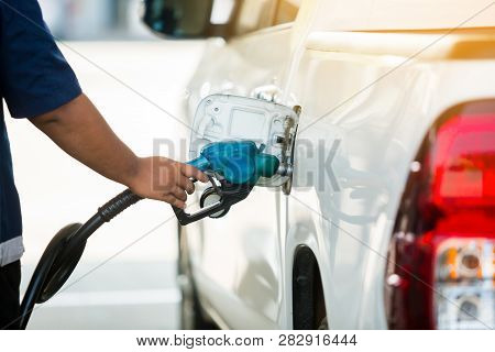 Hand Refilling The White Pickup Truck With Fuel At The Gas Station. Oil And Gas Energy.