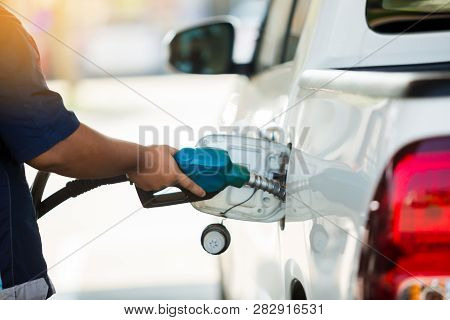 Hand Refilling The White Pickup Truck With Fuel At The Gas Station