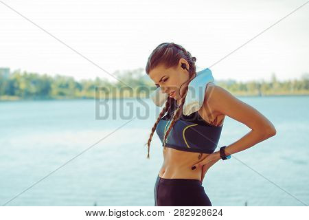 Back Pain. Athletic Woman In Blue Black Sportswear Standing At The Seafront Rubbing The Muscles Of H