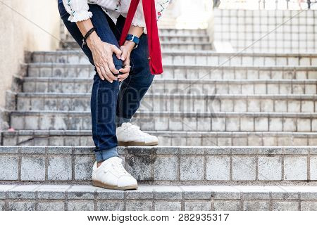 Woman With Painful Knee Struggle Walking Down Flight Of Stairs
