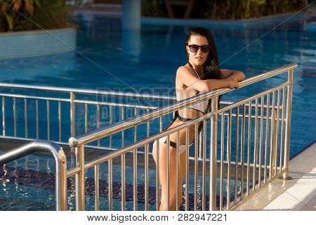 Pretty Young Woman With Long Dark Hair Leaning On A Metal Fence By The Swimming Pool Wearing White S
