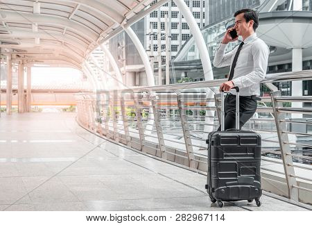 Young Business Man Man On Business Trip Standing With His Luggage And Making A Call Outside Airport.