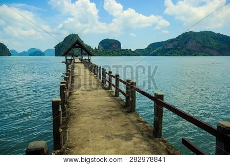 Wooden Pier With A Gazebo At The End, The Shore In The Bay, A Pier For Fishing.
