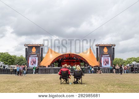 Roskilde, Denmark - July 1, 2016: Two People Sitting In Front Of The Orange Stage At Roskilde Festiv