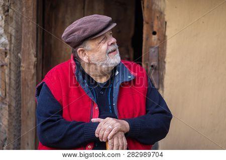 Nice Portrait Of Ukrainian Bearded Senior Peasant Sitting Against Old Barn Entry