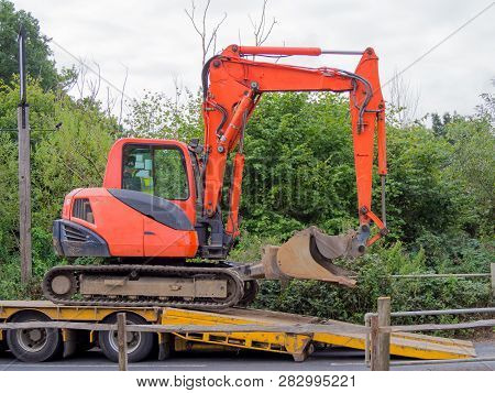 Small Tracked Excavator Being Loaded Onto A Flatbed Transporter.
