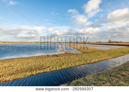 Flooded Polder Landscape In The Winter Season At The End Of A Stormy Day. The Photo Was Taken In The