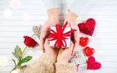 Valentine Gift. Young Couple Hands holding gift box with red bow gift over wooden background. St. Valentine's Day, Love concept. Top view, tabletop. Hands in Hands, romance, dating concept, top view poster