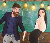Girl on helpless face punished by teacher. Man with beard slapping sexy student, chalkboard on background. Schoolmaster punishes sexy student with slapping on her buttocks with book. Role game concep poster
