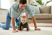family, fatherhood and parenthood concept - happy little baby girl with father at home crawling on floor poster