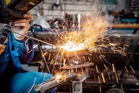 Man Welder In Welding Mask, Building Uniform And Protective Gloves Welds Metal Car Part With Welding