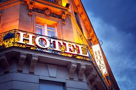 Illuminated hotel sign in Paris at night concept for vacation accomodation and business travel