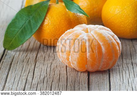 Yellow Sweet Isolated Peeled And Whole Mandarin Clementine Tangerine On Wooden Rustic Vintage Table