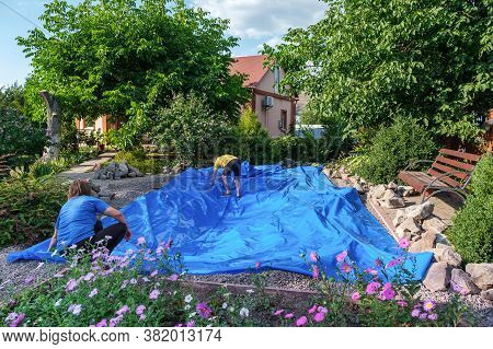 Husband And Wife Lays Blue Hdpe Plastic Film On The Ground To Set Up Fish Pond