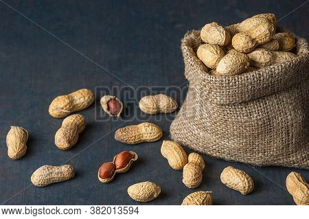 Top View Peanut In Nutshell In Sackcloth Or Burlap Sack On Rustic Background, Composition Of Peanuts