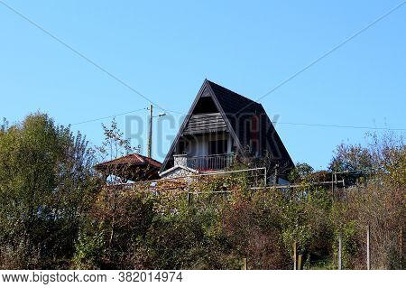 Barely Visible Narrow Vintage Retro Wooden Cottage With Pointy Roof On Top Of Small Hill Next To Woo