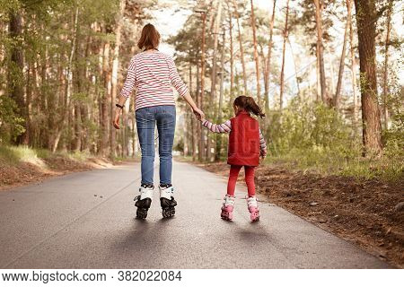 Mother With Daughter Rollerskating In Park, Back View Of Happy Family Spending Time In Active Way In