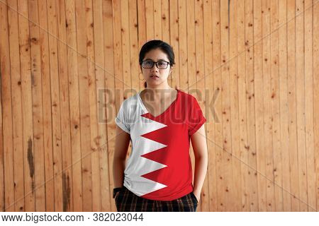 Woman Wearing Bahrain Flag Color Shirt And Standing With Two Hands In Pant Pockets On The Wooden Wal