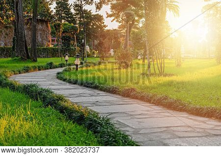 Garden Stone Walkway Winding Among The Green Lawn And Trees In Sunset.  Landscaping In The City Park
