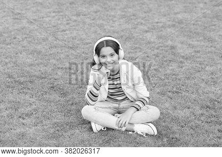 Make It Happen. Listen Music While Relaxing Outdoor. Kid Girl Enjoy Music Green Grass Meadow. Pleasa