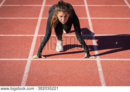Confident Young Fit Woman Sprinter On A Treadmill Rubber Stadium Or Running Track Getting Ready To S