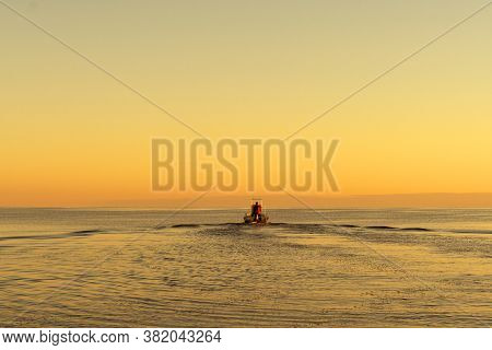 Fisherman On Boat At The Sunset. Beautiful Sunset With The Fishing Boat. Fishing Motor Boat With Ang