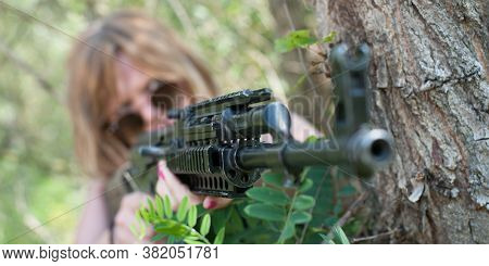 Beautiful And Attractive Woman Soldier Shooting With Rifle Machine Gun In The Forest. Female  Army N