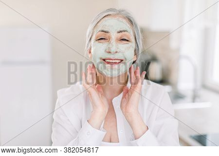 Anti-aging Facial Masks Concept. Copy Space. Headshot Of Attractive Caucasian Elderly Woman With Mud