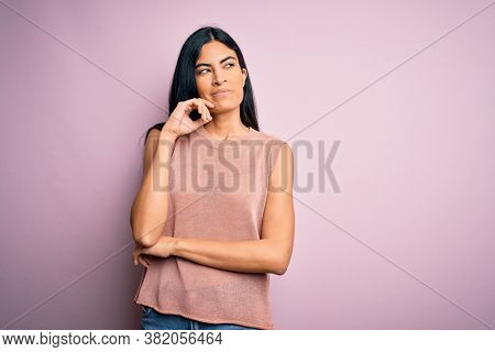 Young beautiful hispanic fashion woman wearing casual sweater over pink background with hand on chin thinking about question, pensive expression. Smiling with thoughtful face. Doubt concept.