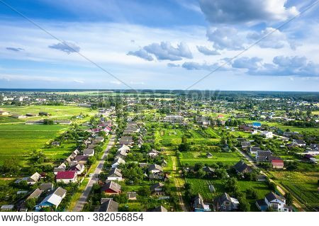 Aerial View Village In Summer Sunny Day. Picturesque View On Fields, Roofs Of Houses, Forest, Blue S