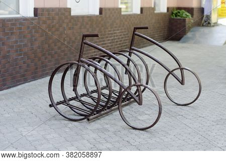Bicycle Iron Parking In The Form Of Bicycles. Street Parking For Personal Or Rented Bicycles. Cyclin