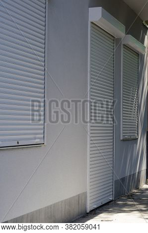 Front Of The Store With Closed White Roller Shutters. The Entrance To The Store And The Windows Are