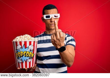 Young handsome african american man watching movie using 3d glasses eating popcorns Showing middle finger, impolite and rude fuck off expression