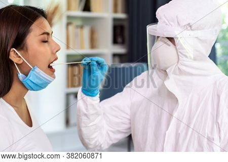 Medical staff with PPE suit test coronavirus covid-19 to asian woman by throat swab at home. New normal health care service at home and medical delivery and COVID-19 testing concept.