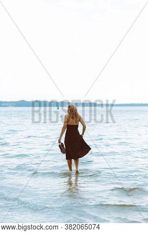 Woman In Black Dress Walking In Water At Sea Beach