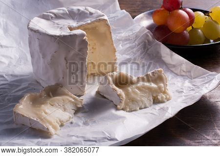 Close Up Of Fresh French Brie Cheese And A One Slice On A A Paper And Grape