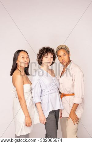 Group of young contemporary females of Asian, African and Caucasian ethnicities standing in front of camera against white background