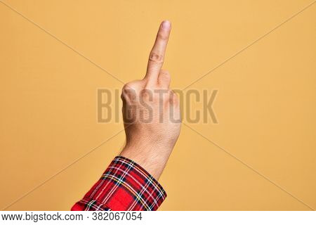 Hand of caucasian young man showing fingers over isolated yellow background showing provocative and rude gesture doing fuck you symbol with middle finger