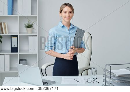 Young successful secretary or head of business company in formalwear holding financial document while standing between desk and armchair