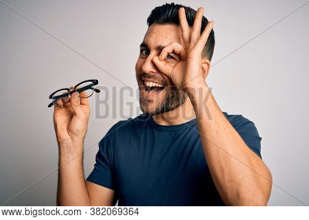Young handsome man holding correction eye glasses over isolated background with happy face smiling doing ok sign with hand on eye looking through fingers