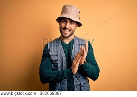 Handsome tourist man with beard on vacation wearing explorer hat over yellow background clapping and applauding happy and joyful, smiling proud hands together