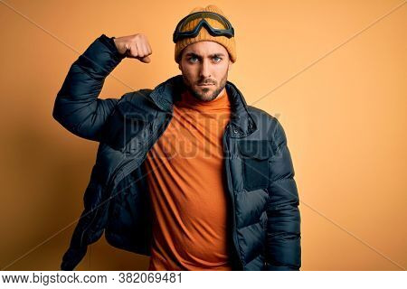 Young handsome skier man with beard wearing snow sportswear and ski goggles Strong person showing arm muscle, confident and proud of power