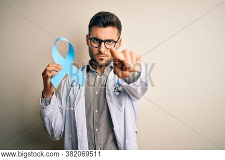 Young professional doctor man holding colon awareness blue ribbon over isolated background pointing with finger to the camera and to you, hand sign, positive and confident gesture from the front