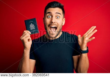 Young handsome tourist man holding canada canadian passport id over red background very happy and excited, winner expression celebrating victory screaming with big smile and raised hands
