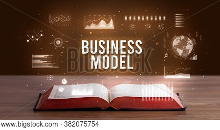 BUSINESS MODEL inscription coming out from an open book, creative business concept