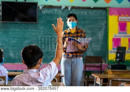 Students And Her Teacher Wearing Protective Face Masks In Classroom At Elementary School After Covid