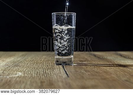 Pure Water Is Poured Into A Beautifal Glass With Bubbles On A Wooden Light Table With A Black Backgr